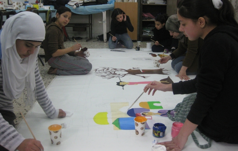 """Students of Al Quds School, Jerusalem, prepare a mural about """"The Palestinan Woman."""" for the Art Miles Project."""