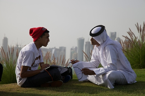 Caption: Rudy Morales, a high school student from New Tech High School in Los Angeles, practices his Arabic with a Qatari student in front of the Doha skyline at the Museum of Islamic Art Park. Photo from U.S. Center for Citizen Diplomacy